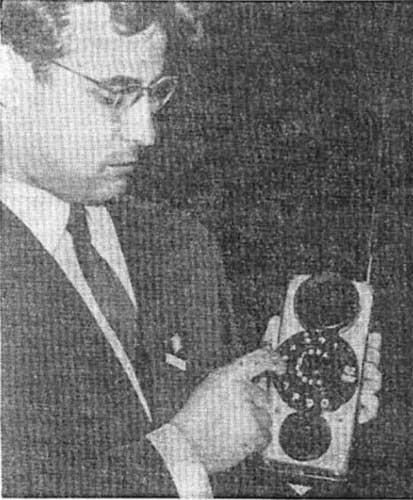 Представитель компании «Радиоэлектроника» демонстрирует мобильный телефон на выставке «Инфорга-65» (Москва)